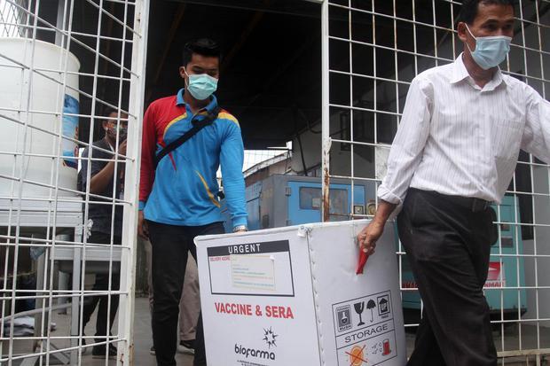 Petugas mengangkat dus berisi vaksin COVID-19 yang akan didistribusikan di Dinas Kesehatan Provinsi Sumatera Barat, Padang, Rabu (13/1/2021). Dinas Kesehatan Provinsi Sumatera Barat mulai mendistribusikan vaksin COVID-19 Sinovac ke dua daerah penerima vak