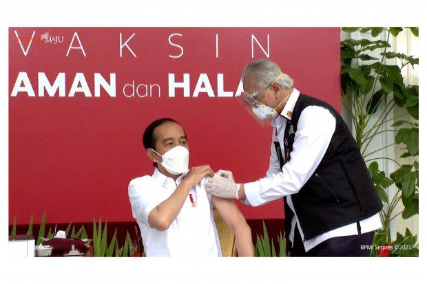 Presiden Indonesia Joko Widodo melakukan vaksinasi Covid-19 di Istana Negara, Rabu (13/1/2021).