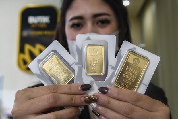Karyawan menunjukan harga emas batangan di Butik Emas Antam, Kebon Sirih, Jakarta, Senin (18/1/2021). Harga emas PT Aneka Tambang (Persero) Tbk pada Senin (18/1) berada pada posisi Rp 944.000 per gram atau turun Rp4.000 dari perdagangan akhir pekan lalu.