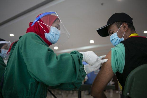 Petugas melakukan vaksinasi kepada tenaga medis di Rumah Sakit Darurat (RSD) Wisma Atlet, Jakarta, Jumat (22/1/2021). Sebanyak 2.630 tenaga kesehatan di RSD Wisma Atlet Kemayoran menjalani vaksinasi COVID-19 secara bertahap. Vaksinasi terhadap para tenaga