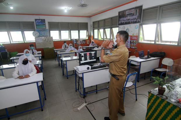Guru dan sejumlah siswa melaksanakan kegiatan belajar tatap muka di SMPN 1 Pontianak, Kalimantan Barat, Senin (22/2/2021). Sebanyak delapan kabupaten/kota di wilayah Kalbar yang berada di zona kuning penyebaran COVID-19 diperbolehkan Pemerintah Provinsi K
