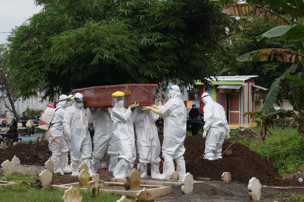 Sejumlah petugas mengusung jenazah untuk dimakamkan dengan protokol COVID-19 di TPU Kelurahan Winongo, Kota Madiun, Jawa Timur, Selasa (23/2/2021). Berdasarkan data Pemprov Jawa Timur terdapat penambahan angka kematian akibat COVID-19 di Jawa Timur pada S