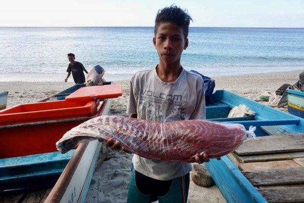 Seorang pemuda membawa hasil tangkapan ikan
