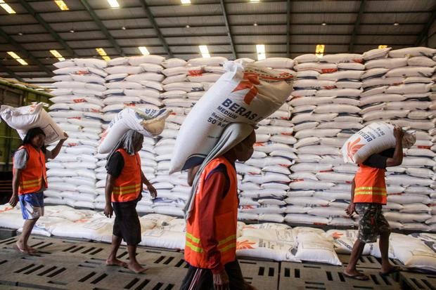 Pekerja mengangkut beras di Gudang Bulog Divre Jatim, Buduran, Sidoarjo, Jawa Timur, Kamis (25/3/2021). Meskipun pemerintah impor beras, Bulog Divre Jatim tetap melakukan penyerapan hasil panen petani di akhir bulan Maret dan pertengahan April dari 1.500