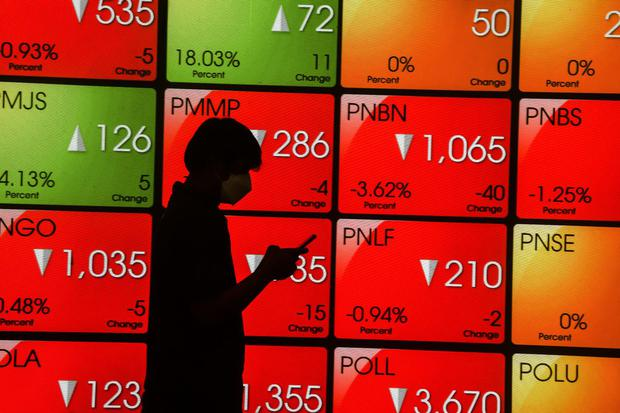 Pekerja melihat telepon pintarnya dengan latar belakang layar pergerakan harga saham di Bursa Efek Indonesia, Jakarta, Rabu (31/3/2021). Indeks Harga Saham Gabungan (IHSG) pada penutupan perdagangan Rabu (31/3) ditutup melemah 85,92 poin atau 1,42 persen