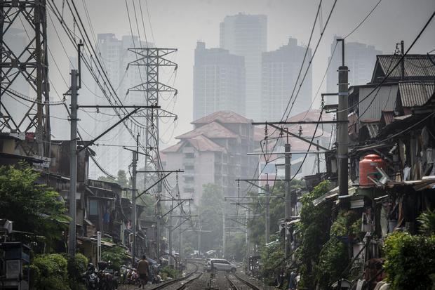"""Deretan permukiman penduduk dengan latar belakang gedung bertingkat tersamar kabut polusi udara di Jakarta, Selasa (20/4/2021). Berdasarkan data """"World Air Quality Index"""" pada Selasa (20/4) pukul 10.00 WIB tingkat polusi udara di Jakarta berada pada ang"""
