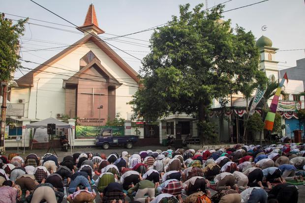 Umat muslim melaksanakan Shalat Idul Fitri 1442 H di Masjid Al Hikmah yang bersebelahan dengan Gereja Kristen Jawa (GKJ) Joyodiningratan, Kratonan, Serengan, Solo, Jawa Tengah, Kamis (13/5/2021). Sebagai bentuk tolaransi umat beragama, Gereja setempat mem