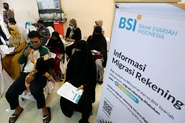 Nasabah antre melakukan migrasi rekening di Bank Syariah Indonesia (BSI) di Banda Aceh, Aceh, Senin (7/6/2021). Pandemi meningkatkan tren hijrah ke perbankan Syariah.