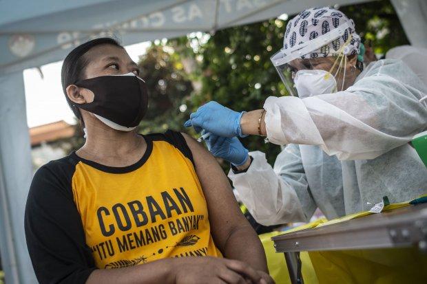 Tenaga kesehatan menyuntikkan vaksin COVID-19 kepada warga Kebon Kacang melalui layanan mobil vaksin COVID-19 keliling di kawasan Kebon Kacang, Tanah Abang, Jakarta, Jumat (9/7/2021). Pemprov DKI Jakarta mengoperasikan 16 mobil vaksin COVID-19 keliling se