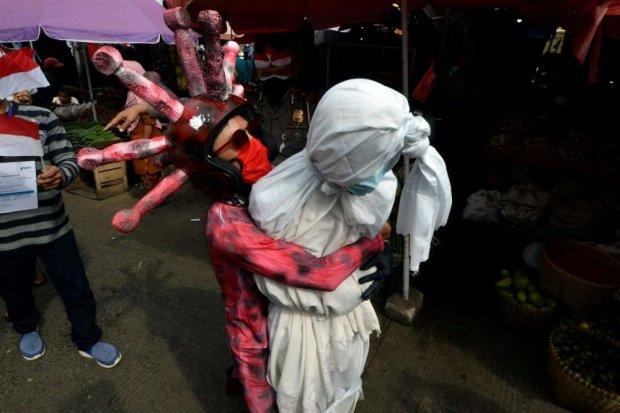 Anggota Satlantas Polresta Bandar Lampung menyosialisasikan bahaya COVID-19 di sejumlah Pasar tradisional di Bandar Lampung, Lampung, Jumat (6/8/2021). Satlantas Polresta Bandar Lampung menggunakan kostum pocong dan berperan sebagai virus Corona serta ten