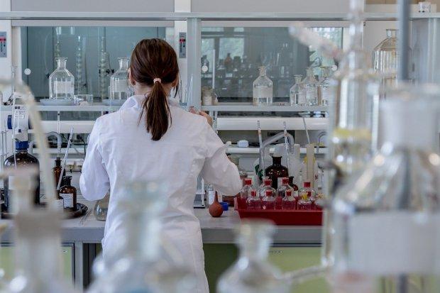 Ilustrasi seorang perempuan sedang melaksanakan eksperimen di laboratorium dengan menerapkan metode ilmiah biologi