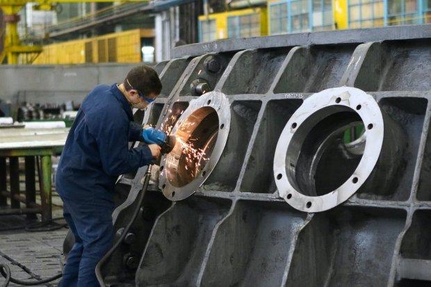Ilustrasi pekerja pabrik membereskan barang produksi yang merupakan masalah ekonomi mikro.