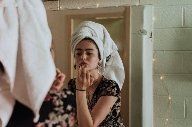 Ilustrasi seorang wanita menerapkan cara memutihkan wajah secara alami