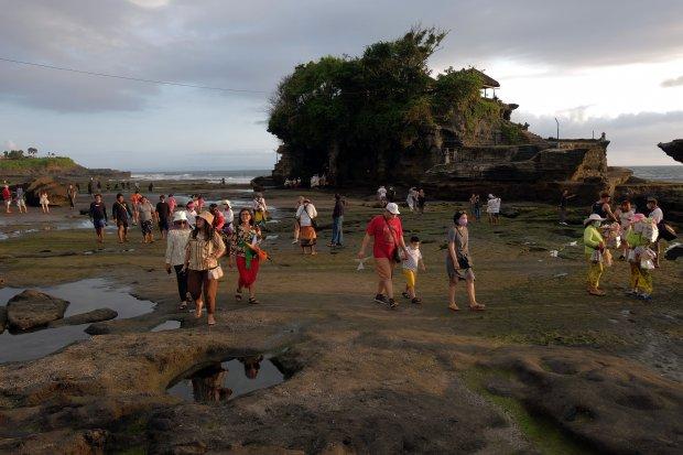 Wisatawan ramai mengunjungi objek wisata Tanah Lot pada pemberlakuan pembatasan kegiatan masyarakat (PPKM) level 3 di Tabanan, Bali, Sabtu (9/10/2021). Banyak dari mereka abai terhadap prokes seperti tidak memakai masker. ANTARA FOTO/Nyoman Hendra Wibowo/