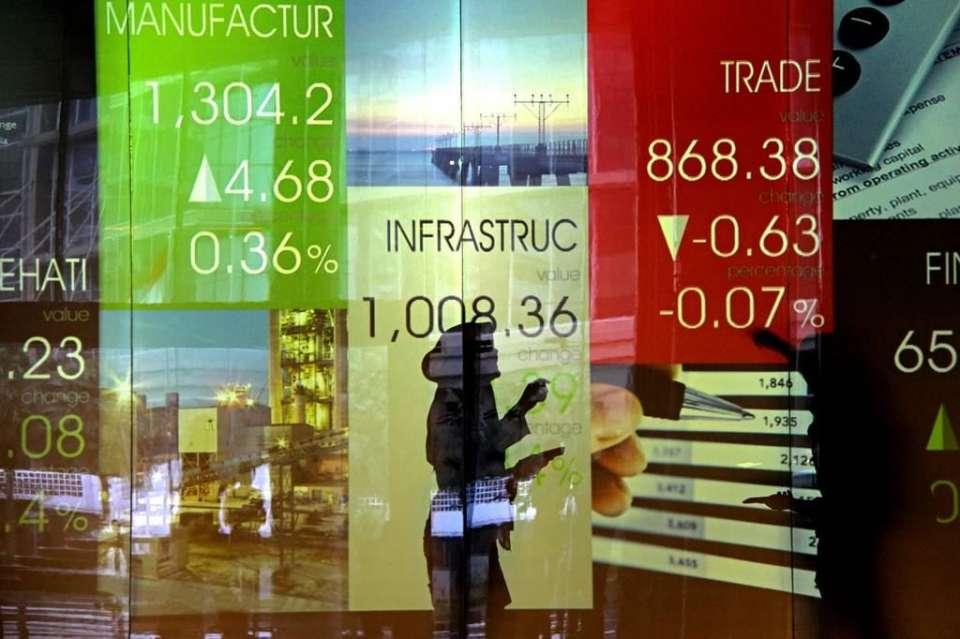 Seorang perempuan sedang mengamati Indeks Harga Saham Gabungan (IHSG). Pada perdagangan Senin (18/11) IHSG ditutup turun tipis 0,09% di level 6.122,62.
